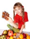 Niño con la píldora de la fruta y de la vitamina. Fotografía de archivo