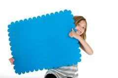 Niño con una muestra azul en blanco Fotos de archivo libres de regalías