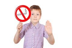 Niño con una muestra que prohíbe fumar, el concepto de Foto de archivo libre de regalías