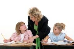 Niño de ayuda del profesor en sala de clase Fotografía de archivo libre de regalías