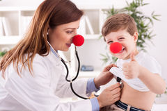 Niño de examen sonriente del éxito del doctor con el finger para arriba Foto de archivo