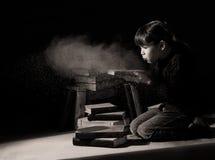 Niño de la muchacha que descubre los libros ocultados en ático Imagenes de archivo