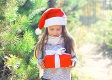 Niño de la niña en el sombrero de santa de la Navidad con la caja de regalo Fotografía de archivo