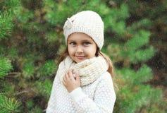 Niño de la niña que lleva el sombrero y el suéter hechos punto con la bufanda cerca del árbol de navidad Imagen de archivo libre de regalías
