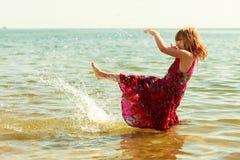 Niño de la niña que salpica en agua del océano del mar Diversión Foto de archivo