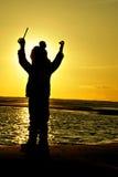 Niño de la puesta del sol de la muchacha de la silueta que juega el mar Imagenes de archivo