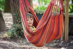 Niño de risa en hamaca Imagen de archivo libre de regalías