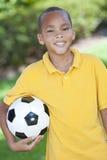 Niño del muchacho del afroamericano y balón de fútbol del balompié Foto de archivo libre de regalías