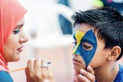 Niño del muchacho joven haciendo su cara pintar para la diversión en una fiesta de cumpleaños Imagenes de archivo
