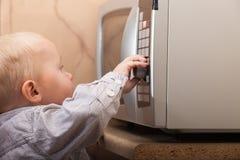 Niño del niño del muchacho que juega con el contador de tiempo del horno de microondas Foto de archivo