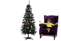 Niño del árbol de navidad en la butaca Fotografía de archivo libre de regalías