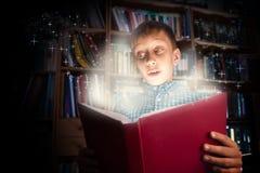 Niño divertido hermoso que sostiene un libro grande con la luz mágica que parece sorprendida Imagen de archivo libre de regalías
