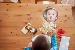 Niño dulce, muchacho, teniendo para los espaguetis del almuerzo en casa, disfrutando de t Imagen de archivo libre de regalías