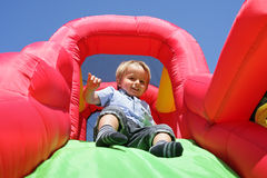 Niño en diapositiva animosa inflable del castillo Fotos de archivo libres de regalías