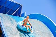 Niño en diapositiva de agua en el aquapark Foto de archivo libre de regalías