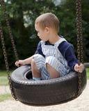 Niño en el oscilación en el patio Imagenes de archivo