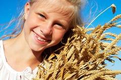 Niño en la camisa blanca que sostiene los oídos del trigo en las manos Fotografía de archivo