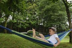Niño en la hamaca con el libro Fotos de archivo libres de regalías