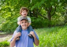 Niño en los hombros del papá. Imagen de archivo