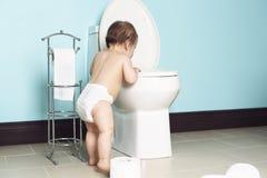 Niño en mirada del cuarto de baño en el retrete Foto de archivo