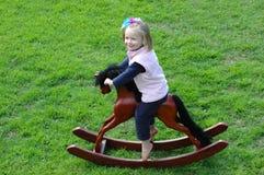 Niño en oscilar-caballo Fotografía de archivo libre de regalías