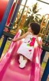 Niño en una diapositiva en patio Fotos de archivo libres de regalías