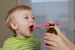 Niño enfermo con el jarabe de la tos Imágenes de archivo libres de regalías