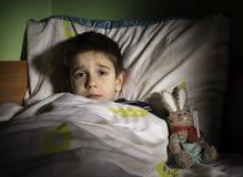 Niño enfermo en cama con el oso de peluche Imagenes de archivo