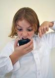 Niño enojado que grita en el teléfono Imagenes de archivo