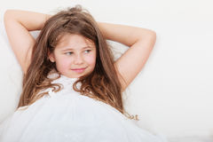 Niño feliz de la niña que se relaja en el sofá Fotografía de archivo