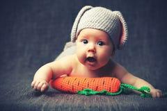Niño feliz del bebé en traje un conejito del conejo con la zanahoria en un gris Foto de archivo libre de regalías