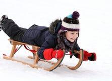 Niño feliz en el trineo en invierno Imágenes de archivo libres de regalías