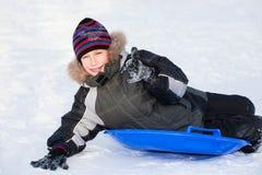 Niño feliz lindo que lleva la ropa caliente sledding y que muestra los pulgares para arriba Fotos de archivo