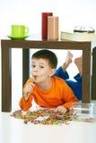 Niño feliz que come la piruleta debajo de los dulces de la tabla derramados Fotos de archivo libres de regalías