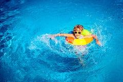 Niño feliz que juega en piscina Imagen de archivo libre de regalías