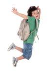 Niño feliz que salta con el morral Imágenes de archivo libres de regalías