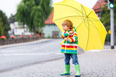 Niño hermoso con el paraguas amarillo y la chaqueta colorida al aire libre Fotografía de archivo
