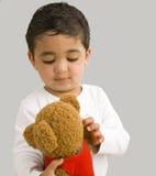 Niño hermoso que juega con un oso del peluche Fotos de archivo libres de regalías