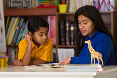 Niño hispánico que aprende leer con la mamá Imagenes de archivo
