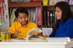 Niño hispánico que aprende leer con la mamá Fotos de archivo libres de regalías
