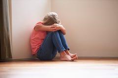 Niño infeliz que se sienta en piso en esquina en casa Imagenes de archivo
