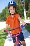 Niño joven del muchacho que completa un ciclo en su bicicleta Fotografía de archivo