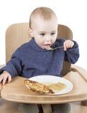 Niño joven que come en alta silla Foto de archivo libre de regalías