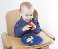 Niño joven que come los melocotones en alta silla Fotografía de archivo libre de regalías