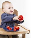 Niño joven que come los tomates en alta silla Foto de archivo