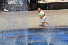 Niño joven que juega en la fuente de agua, playa de Hollywood, Miami, 2014 Fotos de archivo