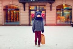 Niño lindo en compras en la estación del invierno Imagen de archivo