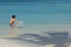Niño masculino joven que salpica el agua en el océano con la sombra de la palmera en Sandy Beach Fotos de archivo