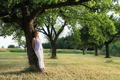 Niño - muchacha que se inclina en árbol Imágenes de archivo libres de regalías