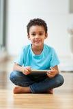 Niño pequeño afroamericano que usa una tableta táctil Imagenes de archivo